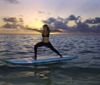 woman doing yoga on a paddle board